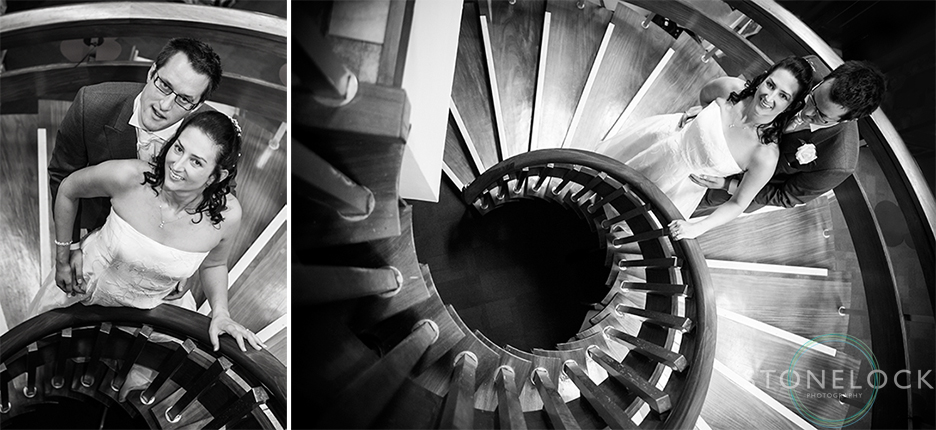 The bride and groom pose for portraits on the spiral staircase at Bourne Hall in Ewell village