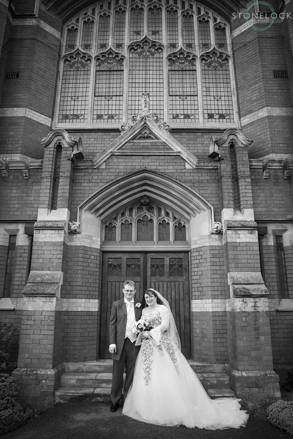 The bride and groom stand outside the church after their