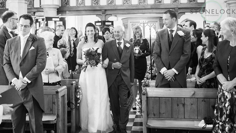 The bride arm in arm with her father walks down the aisle at St Mary's Church in Ewell village