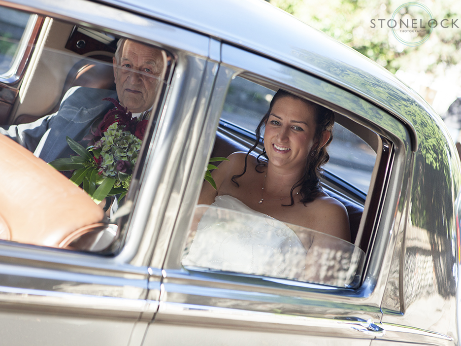 The bride and the father of the bride arrive at St Mary's Church in Ewell village for the wedding ceremony. The wedding car is a bentley