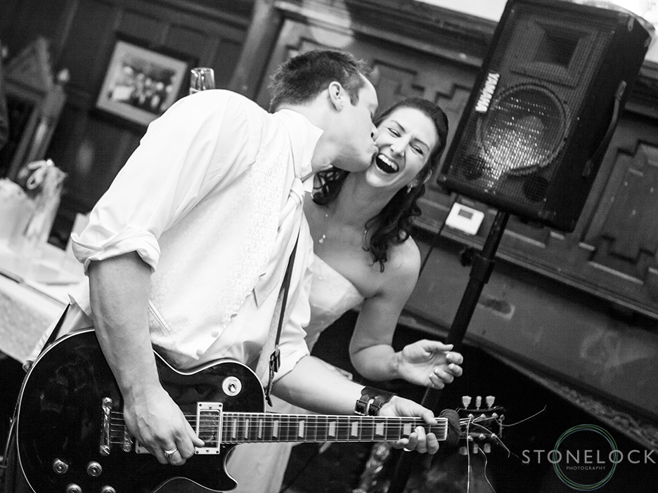 The groom plays the guitar with his band at the wedding reception at the Station Pub in Stoneleigh, the bride leans in for a kiss