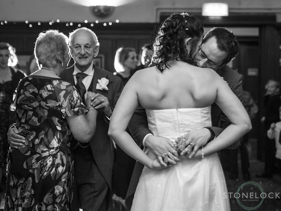 A bride and groom during their first dance, he leans over her shoulder and rests his head, in the background the mother of the bride and father of the bride are dancing, the photo is in black and white
