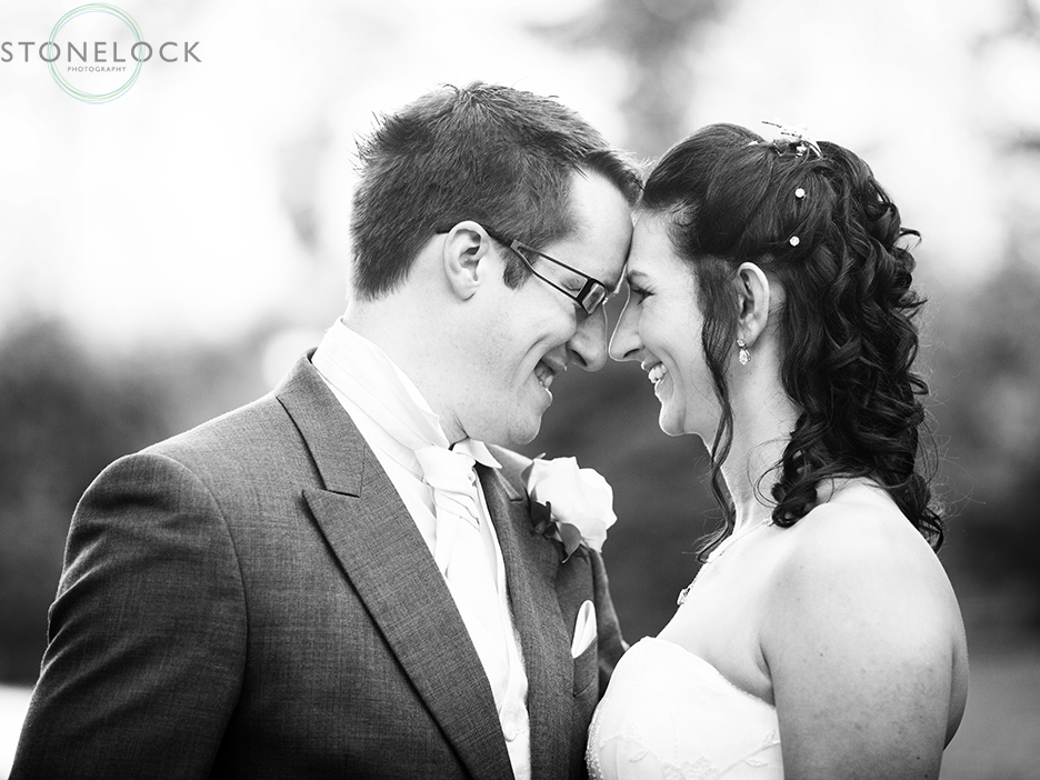 A bride and groom pose for a wedding photo, in black and white they lean towards each other, foreheads touching in a moment of tenderness