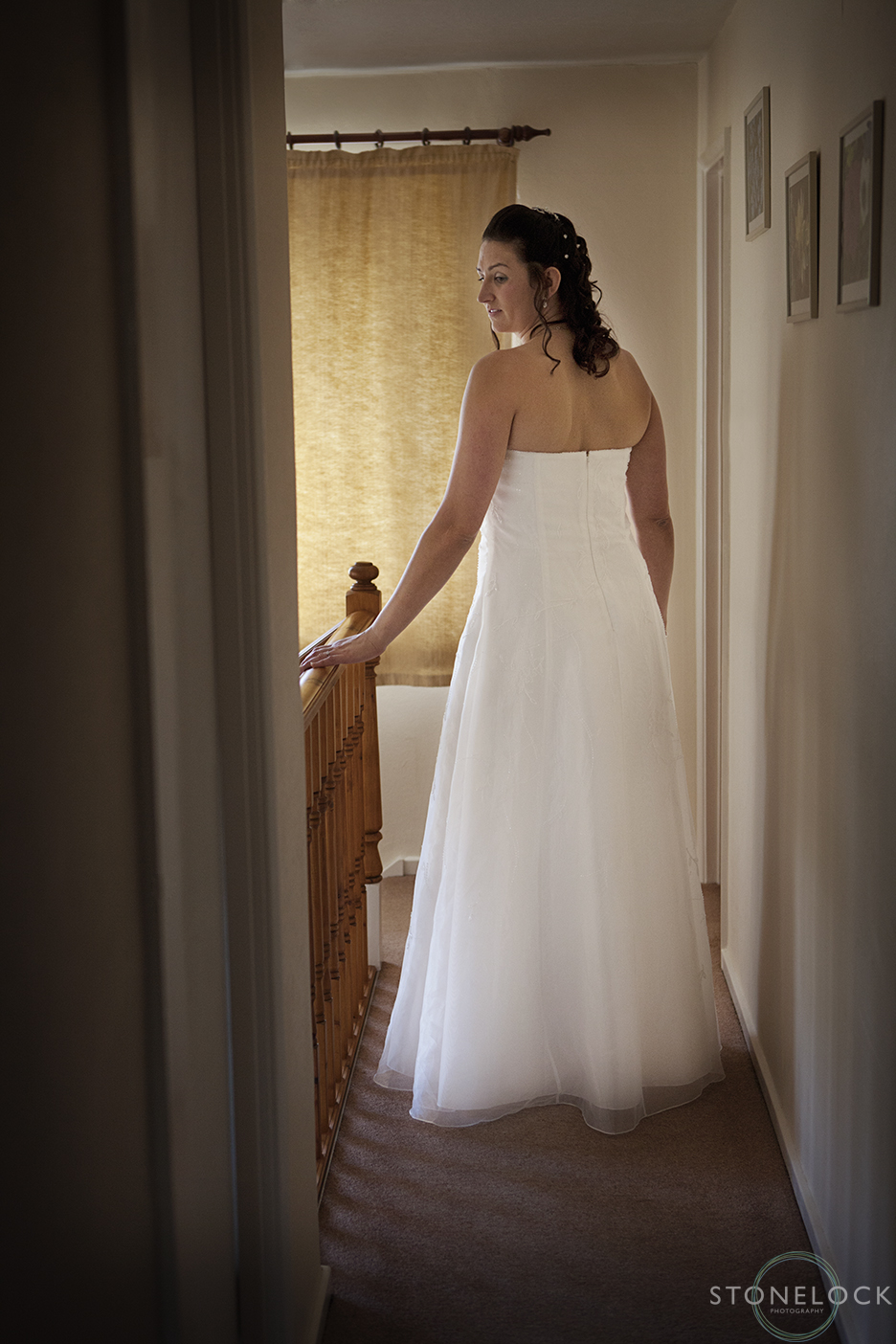 A bride stands at the end of a hallway in her wedding dress lit by a golden sunlight coming through the window
