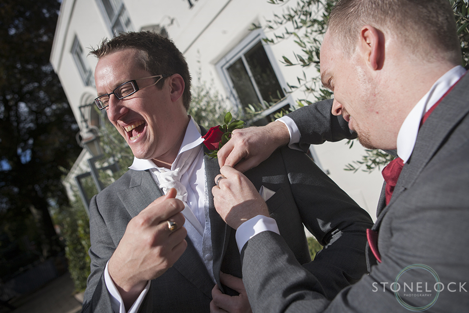 The best man pins the grooms button hole onto his suit before the wedding, the groom laughs as he does this