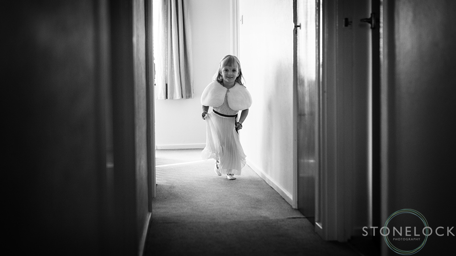 A flower girl runs down the hallway in excitement before the wedding. The photo is in black and white