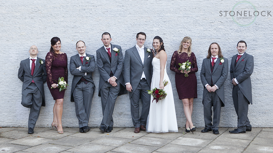 A contemporary photo of the bridal party with the bride and groom, bridesmaids and ushers lined up again a blue wall posing for the camera at Bourne Hall in Ewell