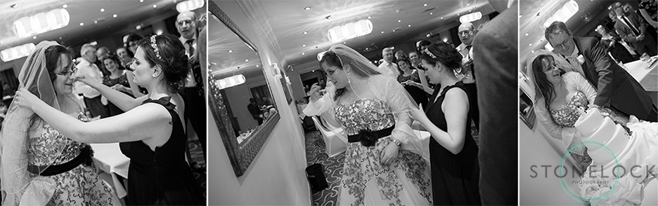 The bride readjusts her veil before cutting the wedding cake