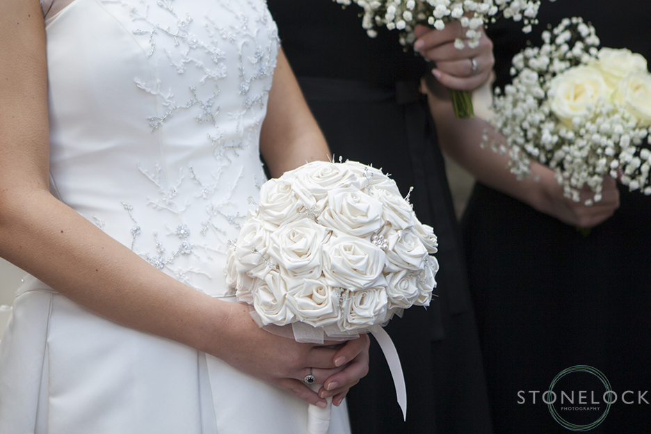 the bride holds her silk flower bouquet for some wedding photos