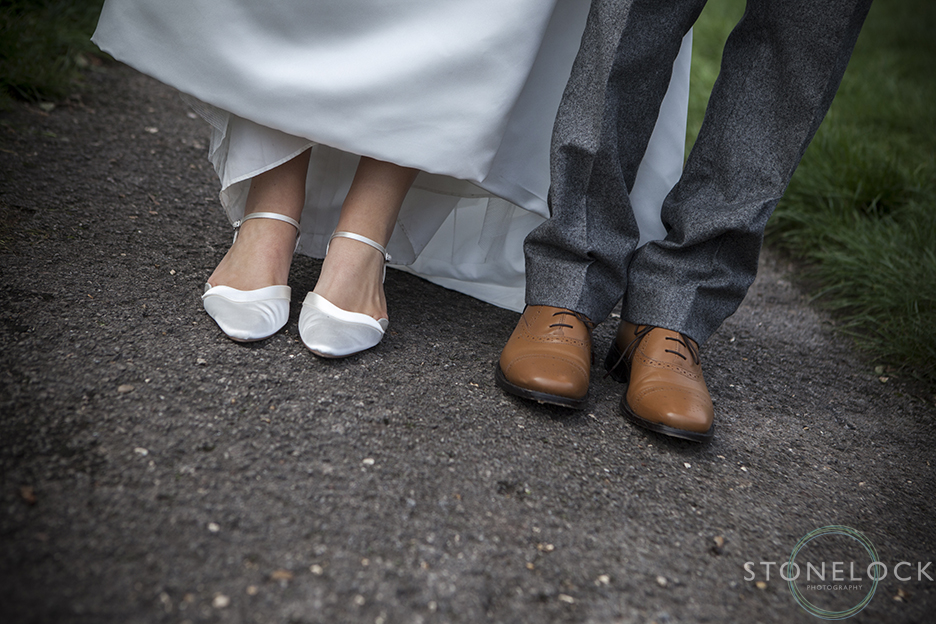 The bride and groom show off their wedding shoes whilst they are having photos taken