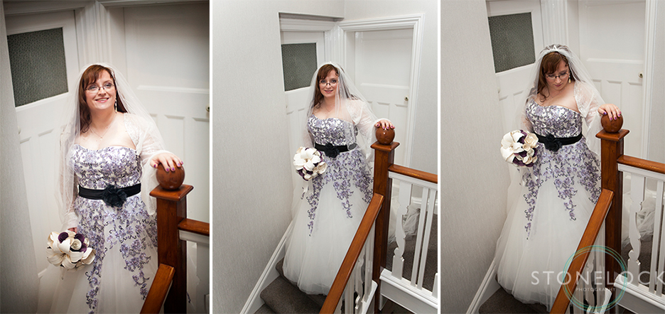 The bride poses for wedding photos at the top of the stairs in her wedding dress
