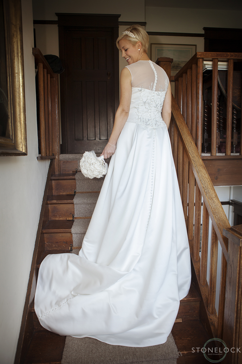 The bride stands on stairs in her wedding dress for some photos before her wedding