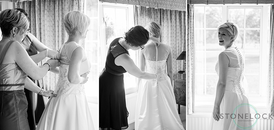 The brides Mum and sister help her put on her dress before her wedding