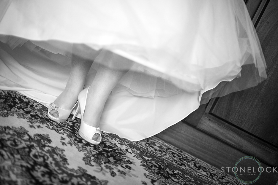 A black and white photo of the brides shoes underneath her dress