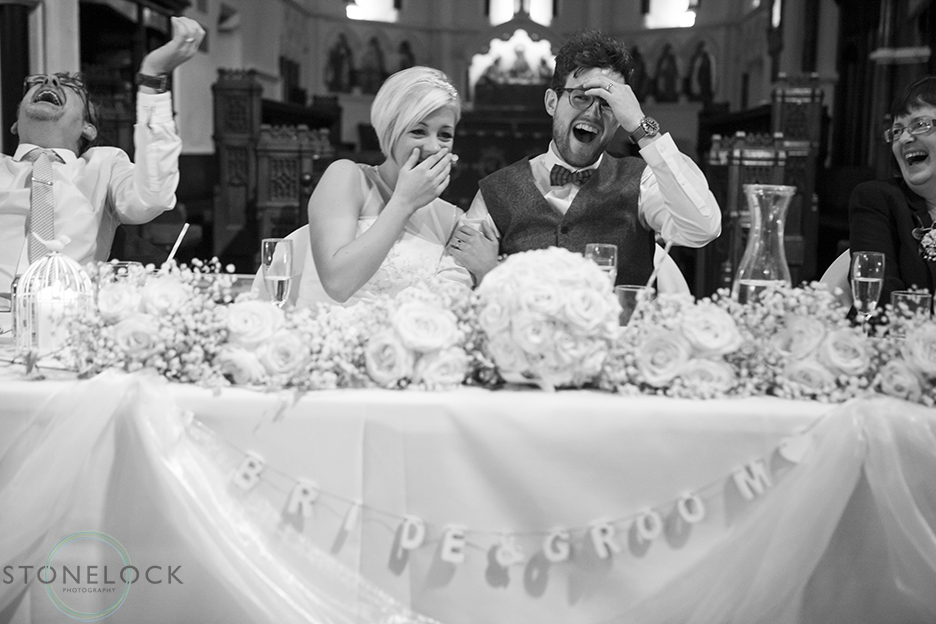 A wedding photo of the bride and groom laughing during the best mans speech at a wedding ceremony at St Mary Magdelene's Church in Bristol