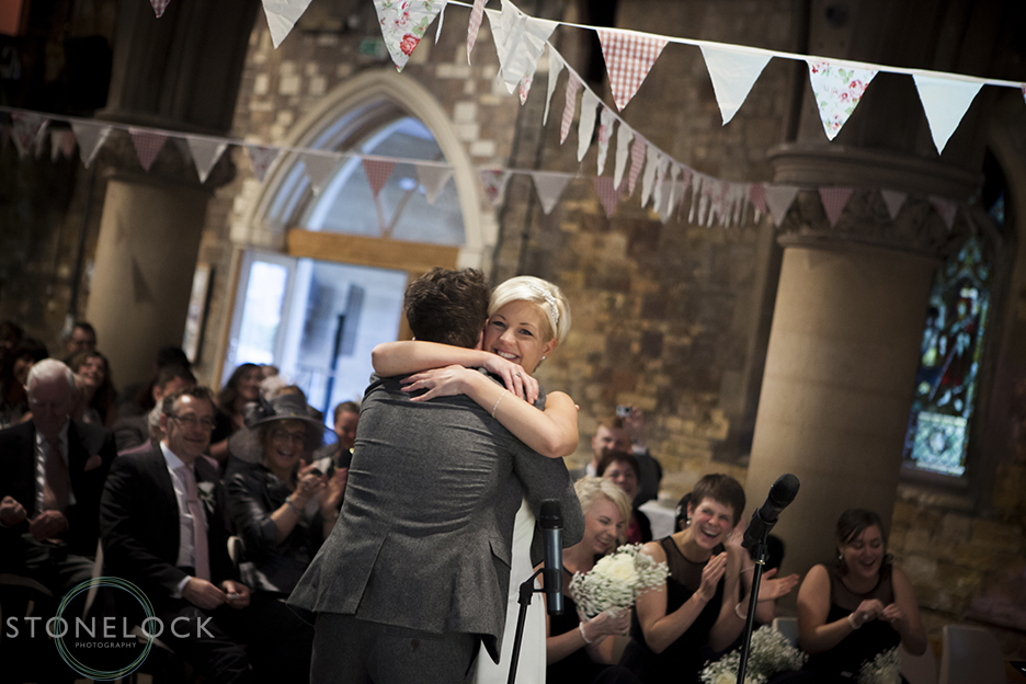 A photo of the bride and groom embracing during their wedding ceremony at Woodlands Church in Bristol