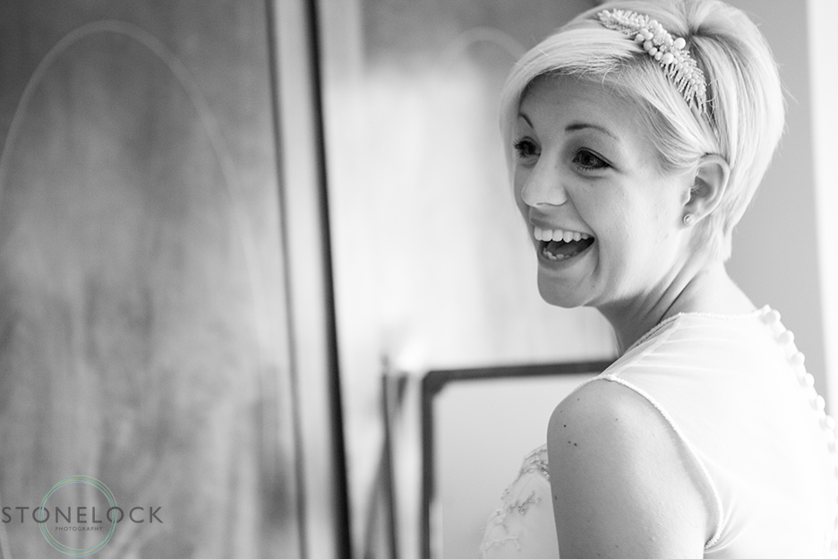 A bride photographed in black and white looks over her shoulder and laughs