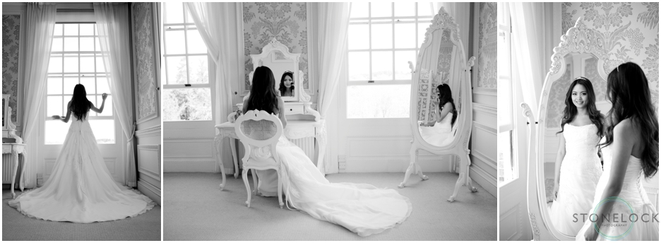 Bride getting ready for her wedding gin a hotel room, she is looking in a mirror