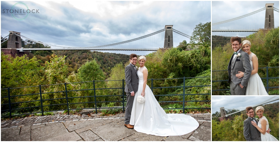 A wedding photo of a bride and groom in front of the Clifton Suspension Bridge in Bristol