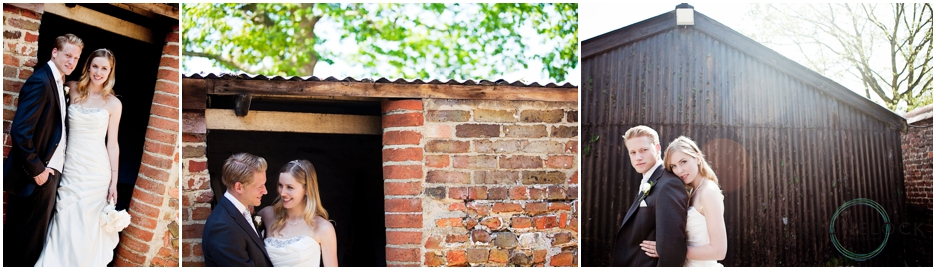 a bride and boom pose for photos in the doorway of a red brick shed