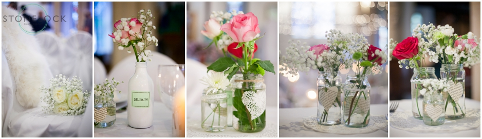 flowers in old jars sit on the tables at a wedding reception