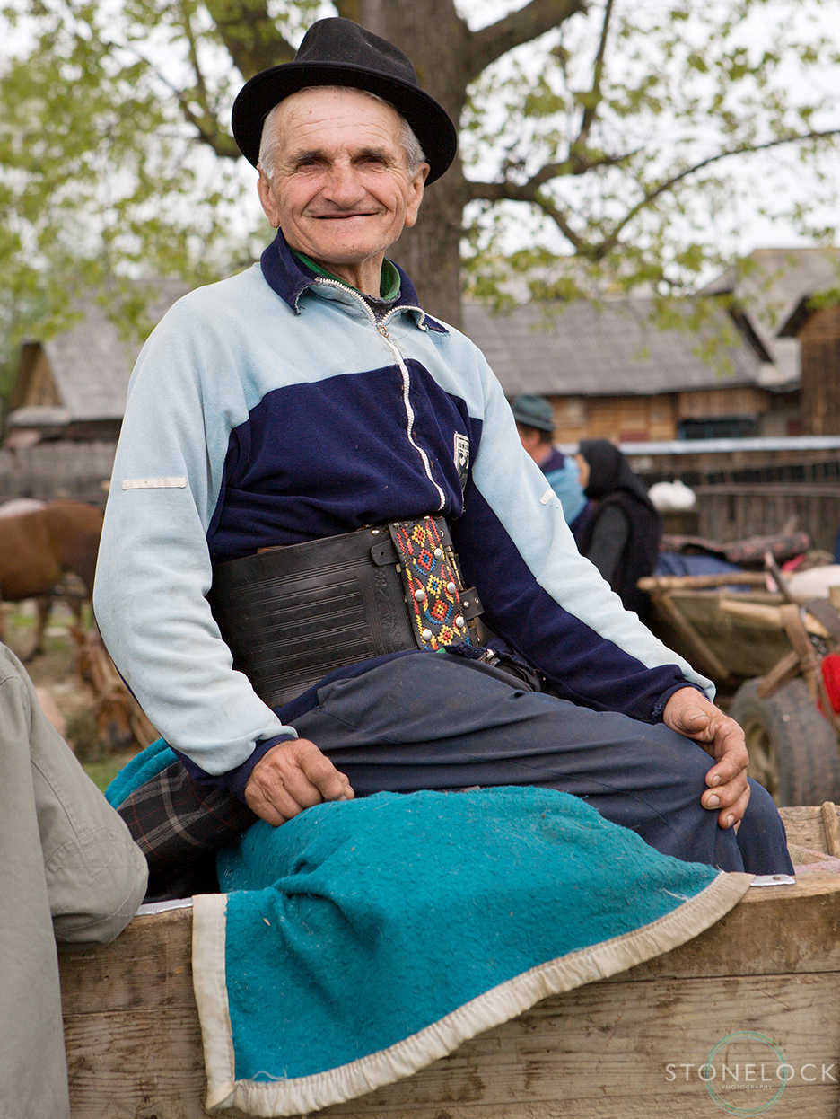 A elderly man sitting on the back of a cart poses for a photo at the Monday morning animal market, Bogdan Voda, Maramures, Romania,
