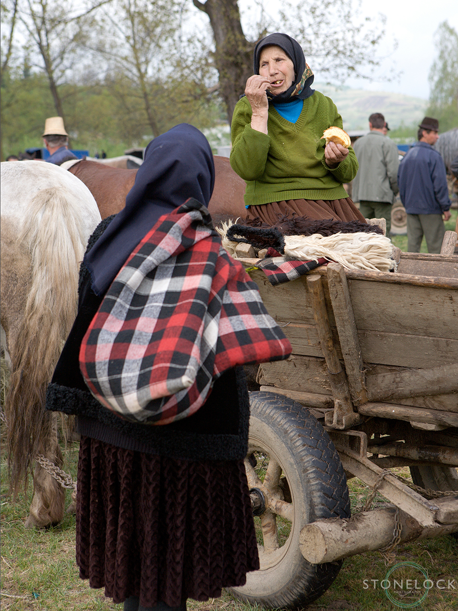 Two elderly women having a chat at the Monday morning animal market, Bogdan Voda, Maramures, Romania,