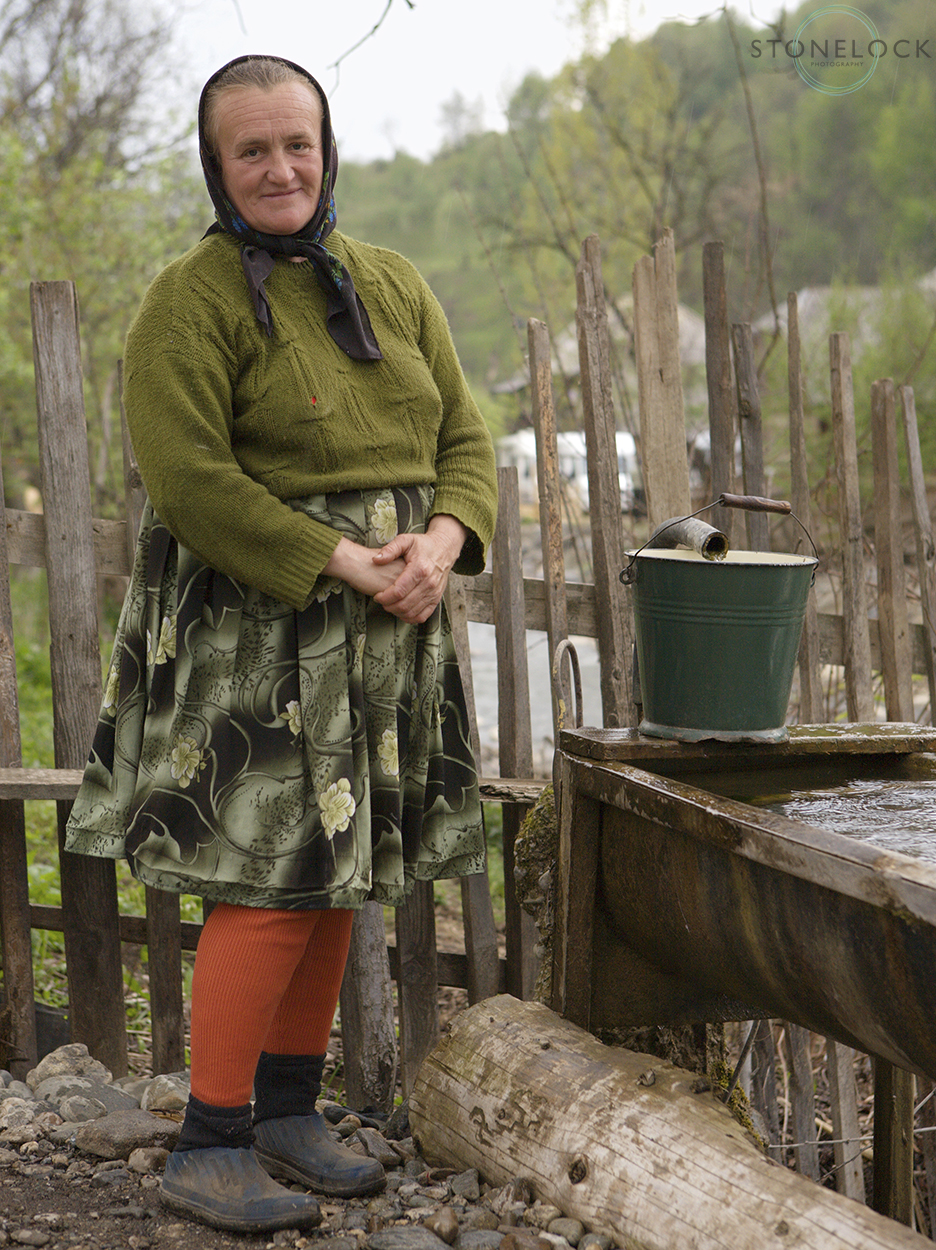 A woman collecting water from the village tap, Botiza Village, Maramures, Romania,
