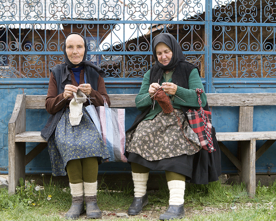 Women sitting on the bench outside their house knitting, Botiza Village, Maramures, Romania,