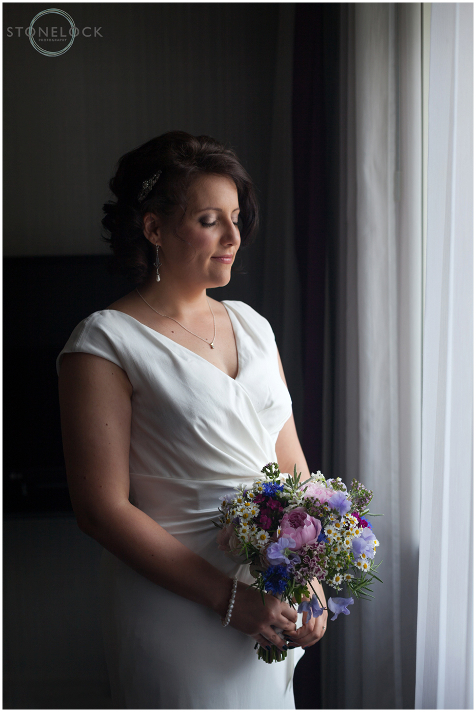A gorgeous photo of a bride standing in from of a window