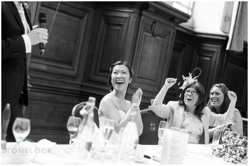 The bride reacts to the grooms speech at their wedding at methodist Central Hall Westminster