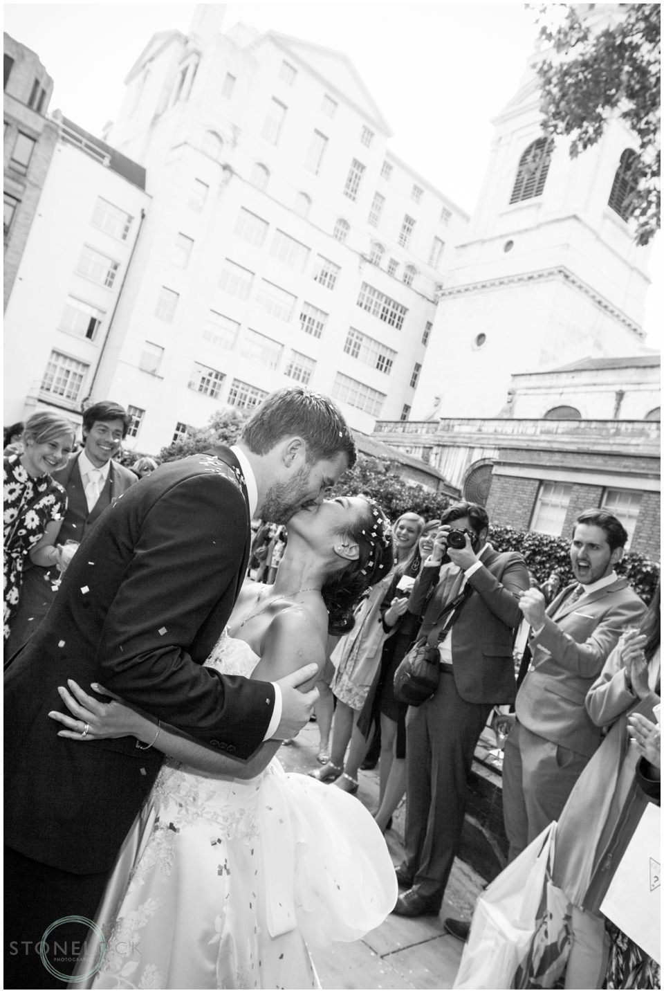 Bride and groom kiss outside St Bride's Foundation in Fleet Street London