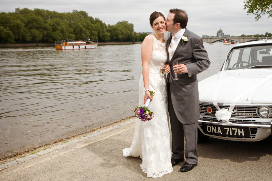 A cheeky kiss for the Bride & Groom by the River Thames in Putney