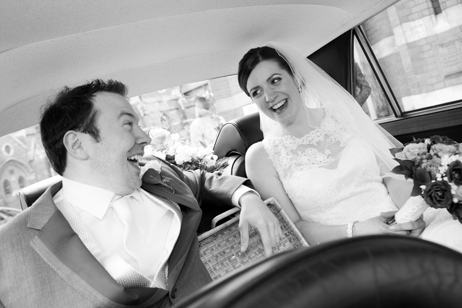 We're married! The Bride & Groom laugh in the wedding car after the wedding ceremony