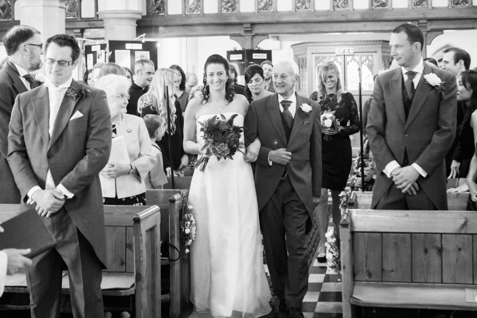 The father of the Bride walks her down the aisle at St Mary's Church in Ewell Village