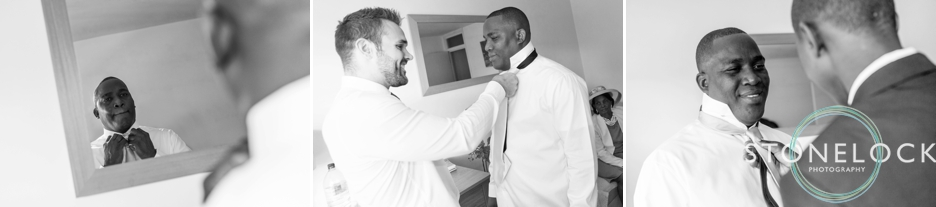 The groom getting ready, the best man helps with his tie
