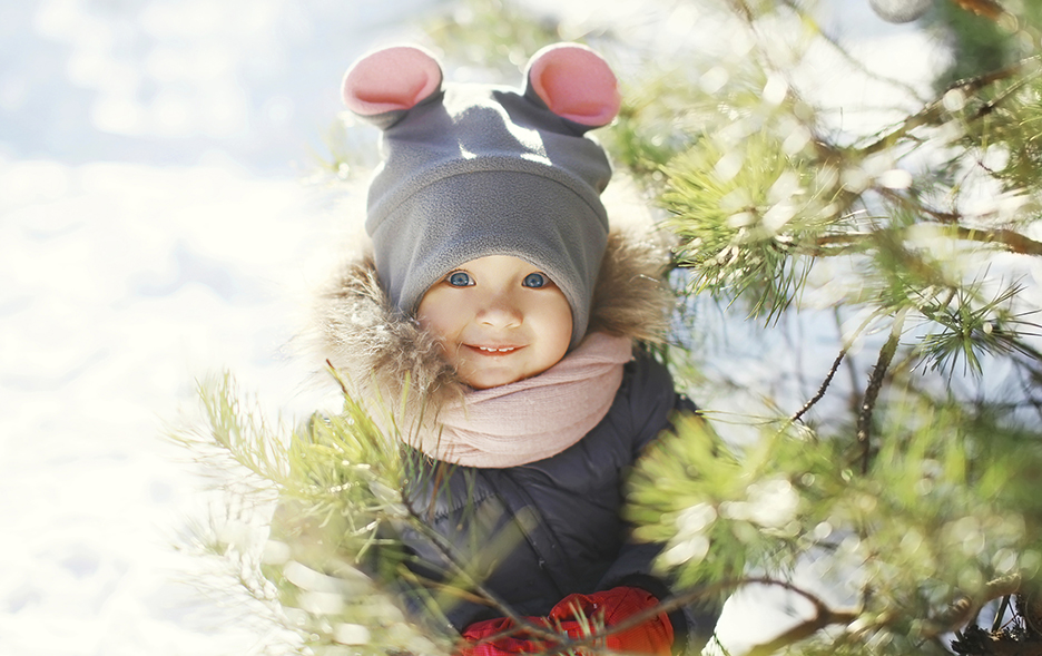 Happy smiling child near christmas tree in winter day