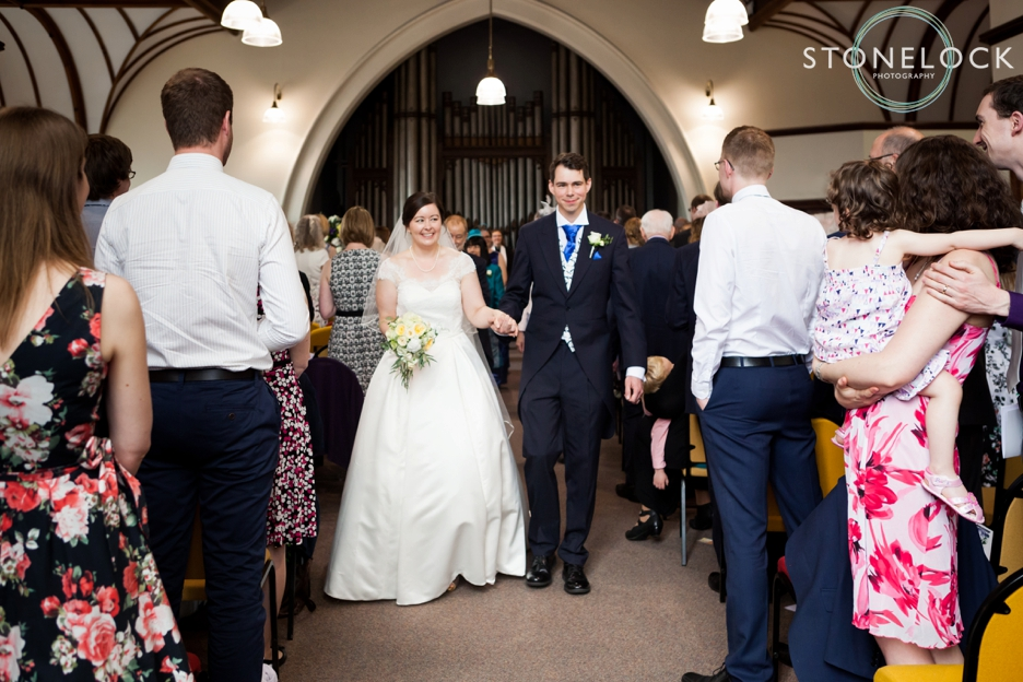 The bride and groom process out after the ceremony at Barnes Methodist Church wedding photography, London, wedding photography
