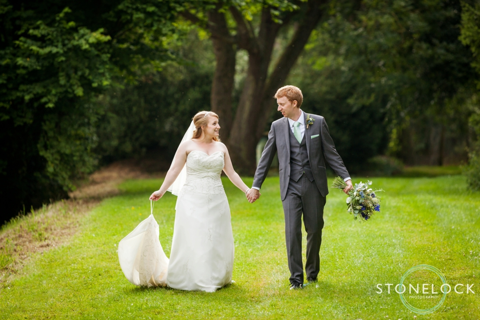 Bride and groom walking at Bassmead Manor Barns in Cambridgeshire for their wedding photography