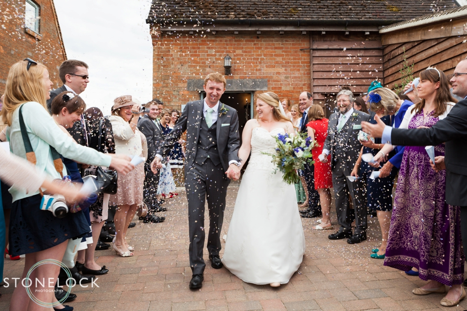 The bride and groom with confetti at Bassmead Manor Barns in Cambridgeshire