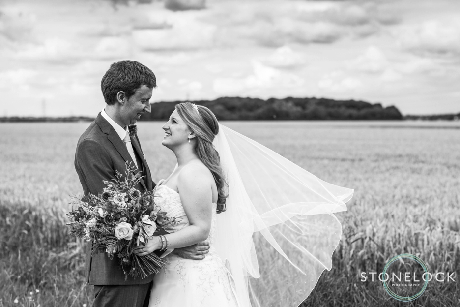 Bride and groom in a cornfield at Bassmead Manor Barns in Cambridgeshire for their wedding photography