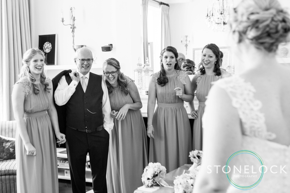 The bridesmaids and father of the bride see the bride as she reveals her wedding dress