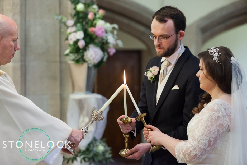 Wedding photography at St Georges Church in Wembley, London, traditional catholic mass, the bride & groom light candles