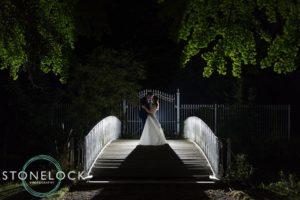 Bride & Groom silhouetted at night on a bridge at Morden Hall Park