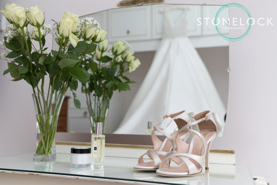 Bride getting ready, her shoes with the dress in the background