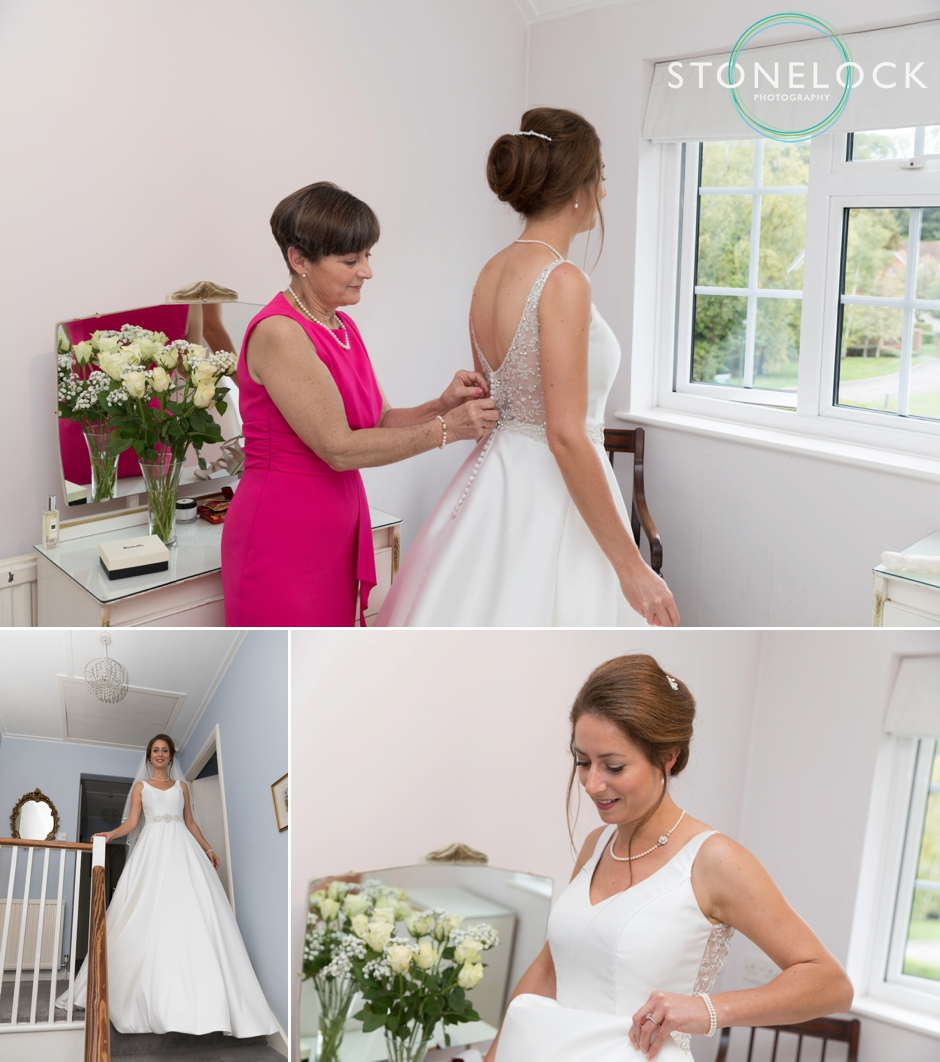 the bride putting on her wedding dress with her mum helping her