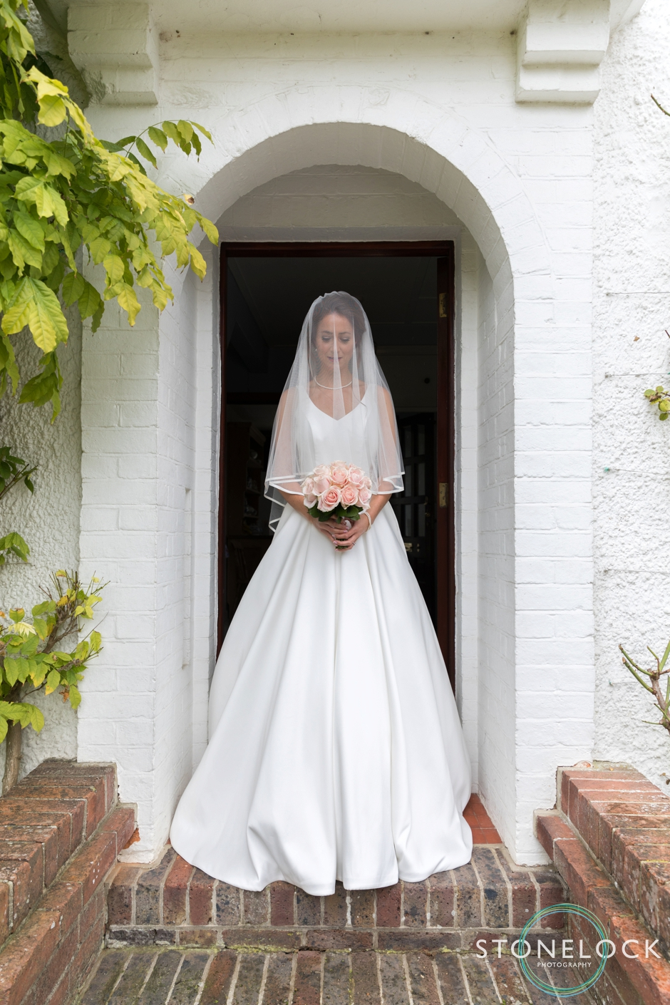 Portrait of a bride with pink roses standing outside her front door