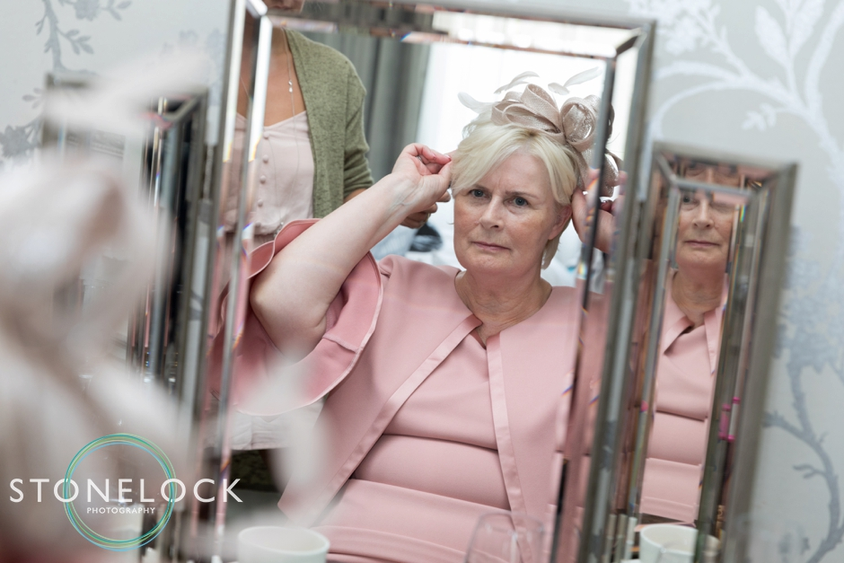 Brides Mum adjusting her hat at Morden Hall Weddings
